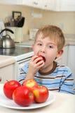 Junger Junge, der einen Apfel isst Lizenzfreies Stockfoto