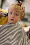Junger Junge, der einen Haarschnitt erhält stockfotos