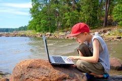 Junger Junge, der einen Laptop verwendet Stockfotos