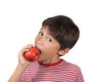 Junger Junge, der einen roten Apfel isst Stockfotos