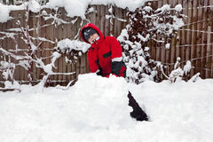 Junger Junge, der einen Schneemann bildet Lizenzfreie Stockfotos