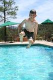Junger Junge, der in einen Swimmingpool lächelt und springt Lizenzfreies Stockbild