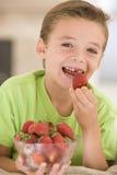 Junger Junge, der Erdbeeren im Wohnzimmer isst Lizenzfreie Stockfotografie