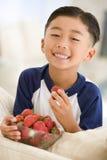 Junger Junge, der Erdbeeren im Wohnzimmer isst Stockfotos