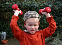 Junger Junge, der für das Leistunganheben sich konzentriert stockfotos