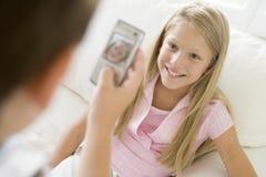Junger Junge, der Foto des lächelnden jungen Mädchens macht Stockbild