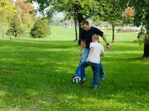 Junger Junge, der Fußball mit seinem Vater spielt Stockfoto