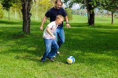 Junger Junge, der Fußball mit seinem Vater spielt Lizenzfreie Stockfotos