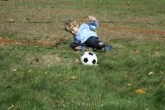 Junger Junge, der Fußball spielt Lizenzfreie Stockbilder