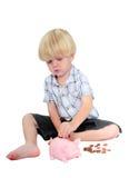 Junger Junge, der Geld in eine piggy Querneigung steckt Stockbild