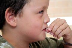 Junger Junge, der geschnittenes Fleisch isst lizenzfreie stockbilder