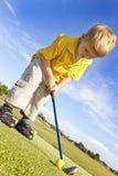 Junger Junge, der Golf spielt Lizenzfreie Stockfotos