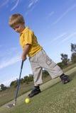 Junger Junge, der Golf spielt Lizenzfreie Stockbilder