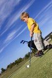 Junger Junge, der Golf spielt Stockfoto