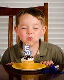 Junger Junge, der heraus Geburtstagkerze durchbrennt Lizenzfreies Stockfoto