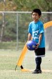 Junger Junge, der im Fußball spielt Lizenzfreie Stockfotos
