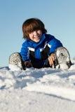 Junger Junge, der im Schnee am Feiertag in den Bergen spielt Stockfotografie