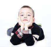 Junger Junge, der im Studio niederlegt Stockfotos