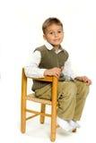 Junger Junge, der im Stuhl sitzt Lizenzfreie Stockfotografie