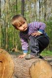 Junger Junge, der im Wald spielt Stockbild