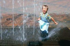 Junger Junge, der im Wasserbrunnen spielt Stockbilder
