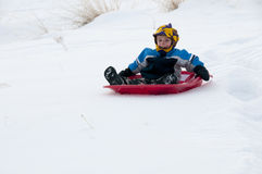 Junger Junge, der im Schnee sledding ist Stockfotografie