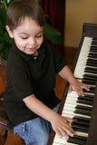 Junger Junge, der Klavier spielt Stockbild