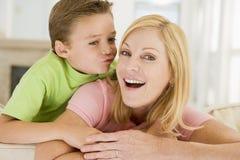 Junger Junge, der lächelnde Frau im Wohnzimmer küßt Stockbilder