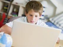 Junger Junge, der Laptop in seinem Schlafzimmer verwendet Stockbilder