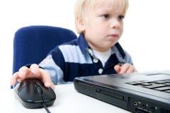 Junger Junge, der Laptop verwendet Stockfotos