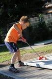 Junger Junge, der Minigolf spielt Lizenzfreies Stockbild