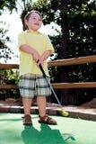 Junger Junge, der Minigolf spielt Lizenzfreie Stockfotos