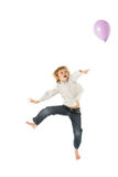 Junger Junge, der mit Ballon im Studio springt Stockbilder