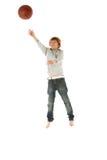 Junger Junge, der mit Basketball im Studio springt Stockfotos