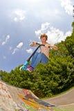 Junger Junge, der mit einem Roller Bord geht Stockbild