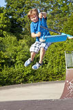 Junger Junge, der mit einem Roller Bord geht Lizenzfreies Stockfoto