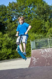 Junger Junge, der mit einem Roller Bord geht Stockfotos