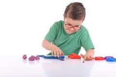 Junger Junge, der mit Formungslehm spielt stockbild
