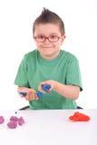 Junger Junge, der mit Formungslehm spielt stockfotos