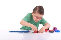 Junger Junge, der mit Formungslehm spielt Lizenzfreie Stockbilder