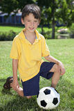 Junger Junge, der mit Fußball-oder Fußball-Kugel spielt Stockfotografie