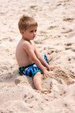 Junger Junge, der mit Sand spielt Lizenzfreies Stockbild