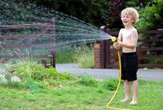 Junger Junge, der mit Schlauchleitung und Wasser spielt Lizenzfreie Stockbilder