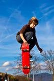 Junger Junge, der mit seinem Skateboard Bord geht Lizenzfreie Stockfotografie