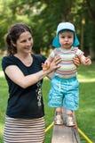 Junger Junge, der mit seiner Mutter auf der Bank geht Stockbild