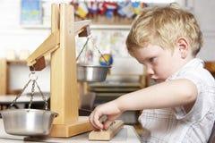 Junger Junge, der an Montessori/am Vortraining spielt lizenzfreie stockfotos