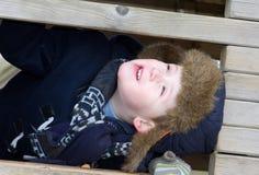 junger Junge, der am Park an einem kalten Tag spielt Stockfoto