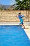 Junger Junge, der in Pool springt Stockfotografie