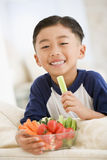 Junger Junge, der Schüssel Gemüse im Wohnzimmer isst stockbilder