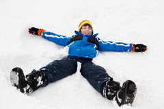 Junger Junge, der Schnee-Engel auf Steigung bildet Lizenzfreie Stockfotos